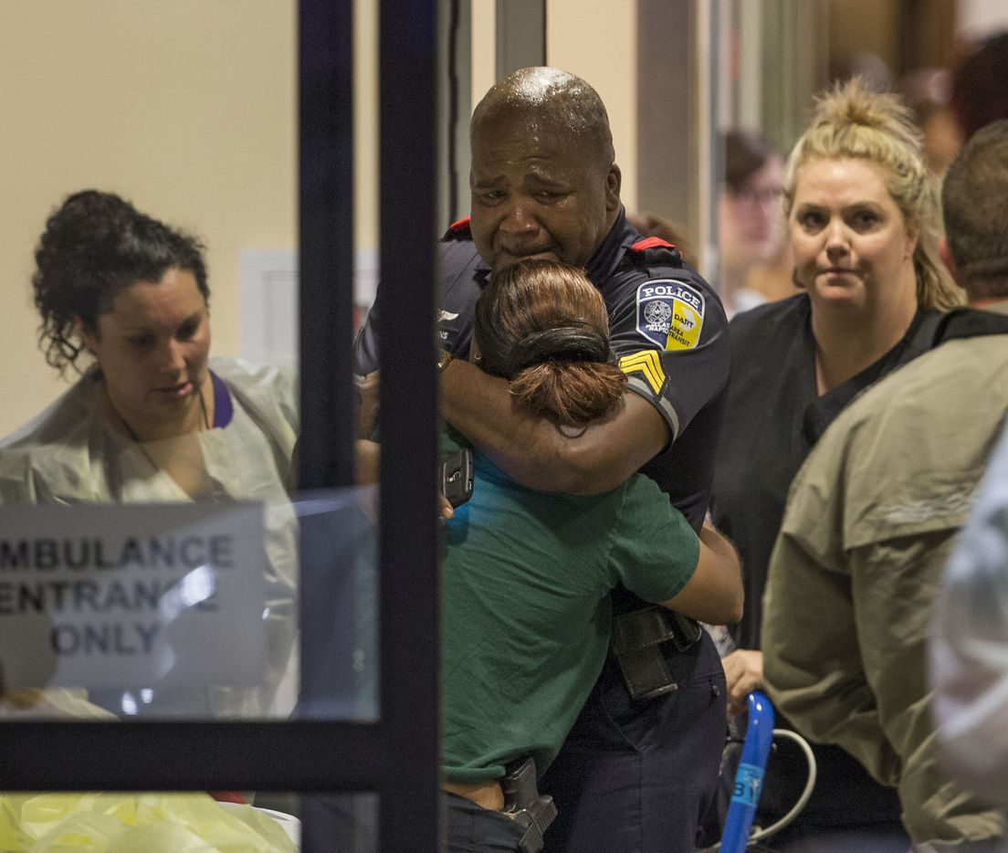 A DART police officer receives comfort outside a Baylor University Medical Center at Dallas emergency room. (Ting Shen/Staff Photographer)