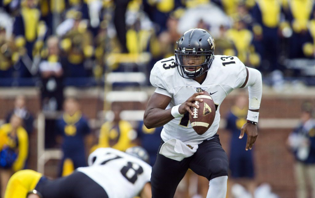 Central Florida quarterback Justin Holman (13) scrambles with the ball in the first quarter of an NCAA college football game against Michigan, Saturday, Sept. 10, 2016,  at Michigan Stadium in Ann Arbor, Mich. (AP Photo/Tony Ding)