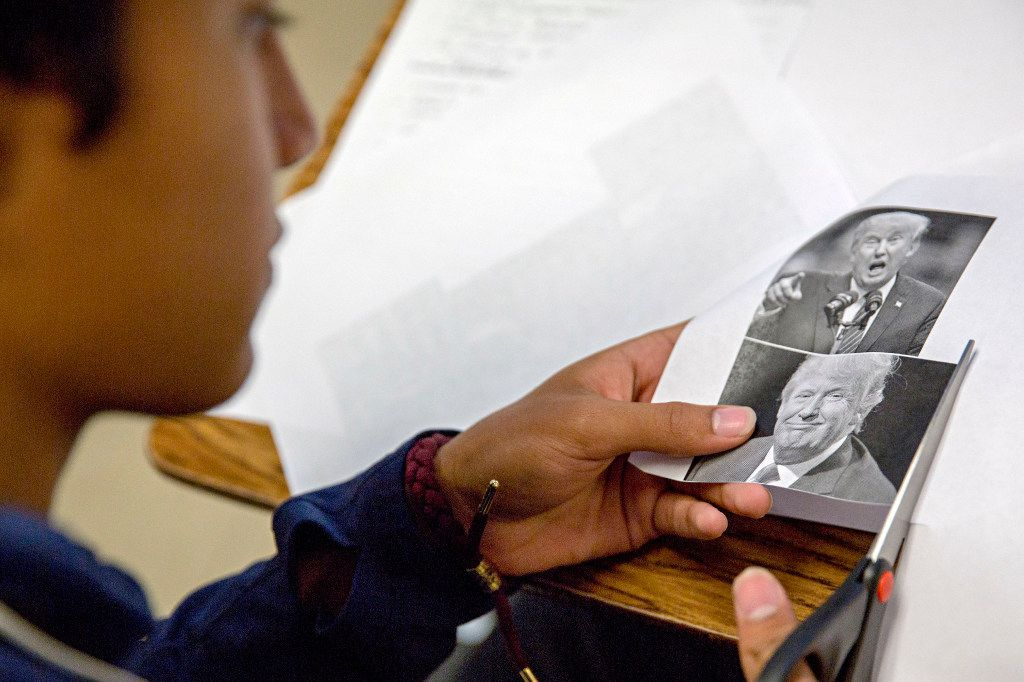 Misael Mancia cut out photos of Donald Trump as he and other students made posters of presidential candidate platforms during a class at Irving High School this week. (G.J. McCarthy/Staff Photographer)