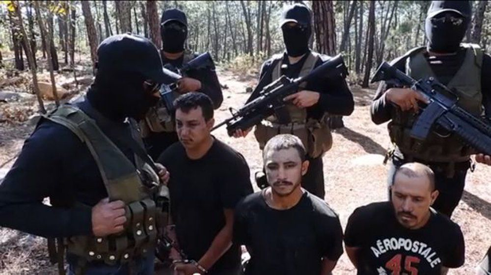 The Jalisco New Generation Cartel posted a video early in 2015 showing masked members of the cartel with prisoners from a rival gang. (Image from video)