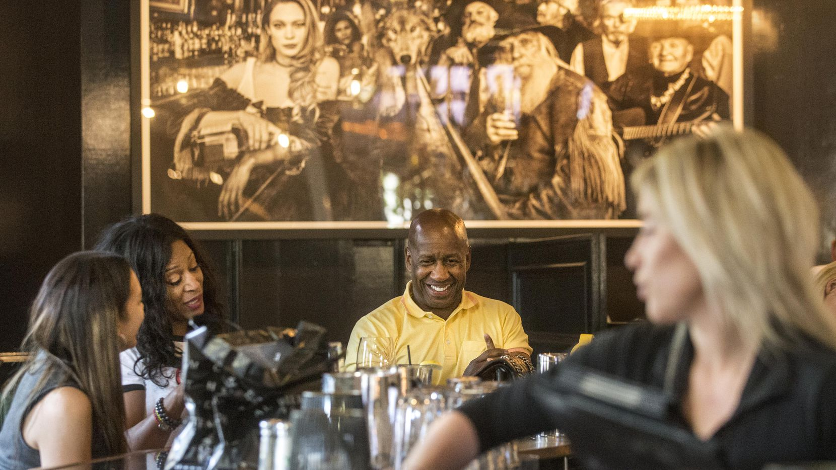From left, Annette Watkins, Stephene (cq) Tolocko and C.A. Anderson, all of Dallas, talk while Abbey Jayne, an employee, wipes the bar clean at Al Biernat's in Dallas on Aug. 1, 2018. Al Biernat's has been participating in Restaurant Week for over 20 years. (Carly Geraci/The Dallas Morning News)