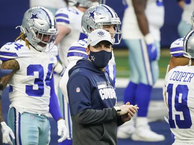 Dallas Cowboys offensive coordinator Kellen Moore watches the team warm up before an NFL football game against the Philadelphia Eagles at AT&T Stadium on Sunday, Dec. 27, 2020, in Arlington.