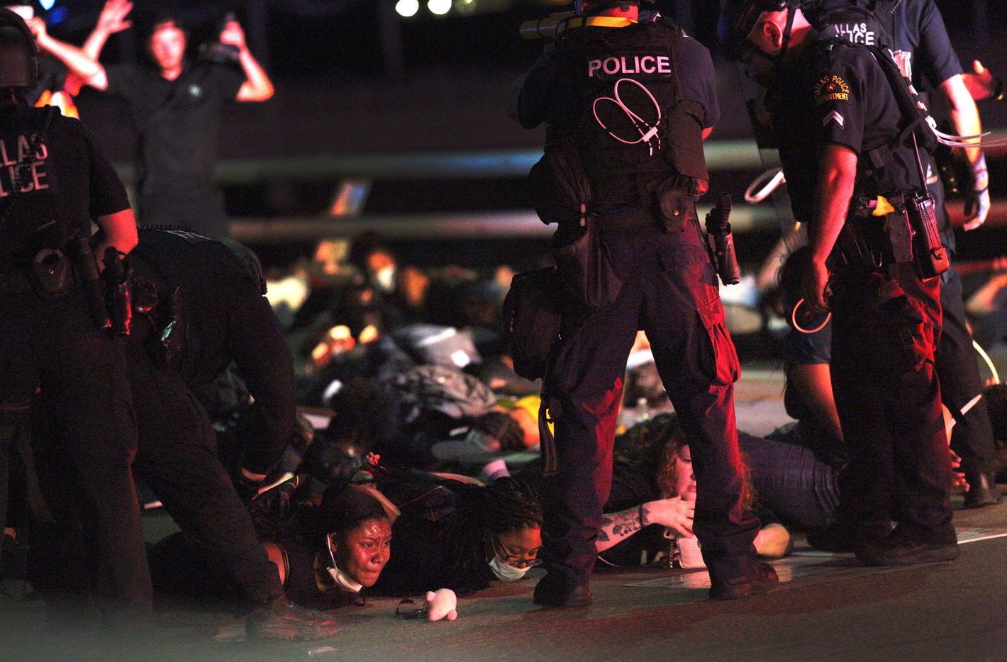 Police have protestors lie on the ground on the Margaret Hunt Hill bridge, while arresting them after curfew while they marched against police brutality on Monday, June 1, 2020, in Dallas.
