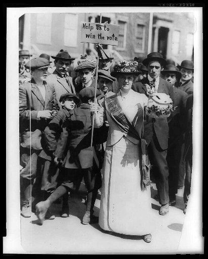 """Mrs. Suffern,"" holds a vote sign as a crowd of men and boys watch, c. 1914. (Library of Congress/MCT)"