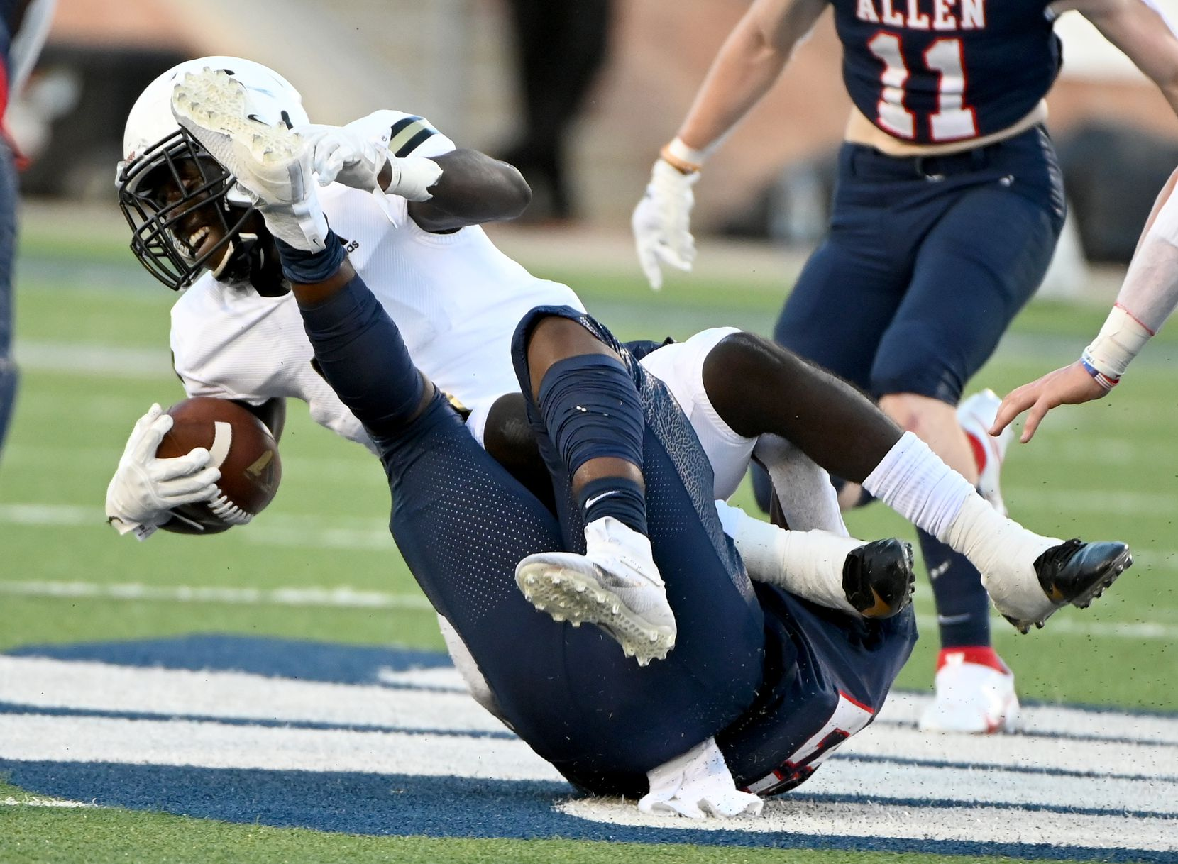 Plano East Ismail Mahdi, in white, is tackled by Allen's Michael Momoh in the first half during a high school football game between Plano East and Allen, Friday, Aug. 27, 2021, in Allen, Texas. (Matt Strasen/Special Contributor)