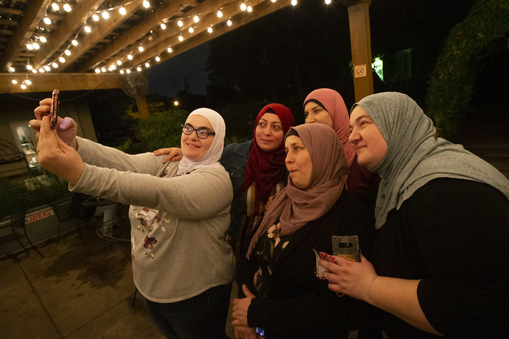The community cooks from Syria, Chechnya and Turkey take a selfie following the Break Bread Break Borders dinner event honoring World Food Day at the Garden Cafe in Old East Dallas on Tuesday, Oct. 15, 2019. The women shared an evening of food, culture and storytelling from around the world with attendees. (Lynda M. Gonzalez/The Dallas Morning News)