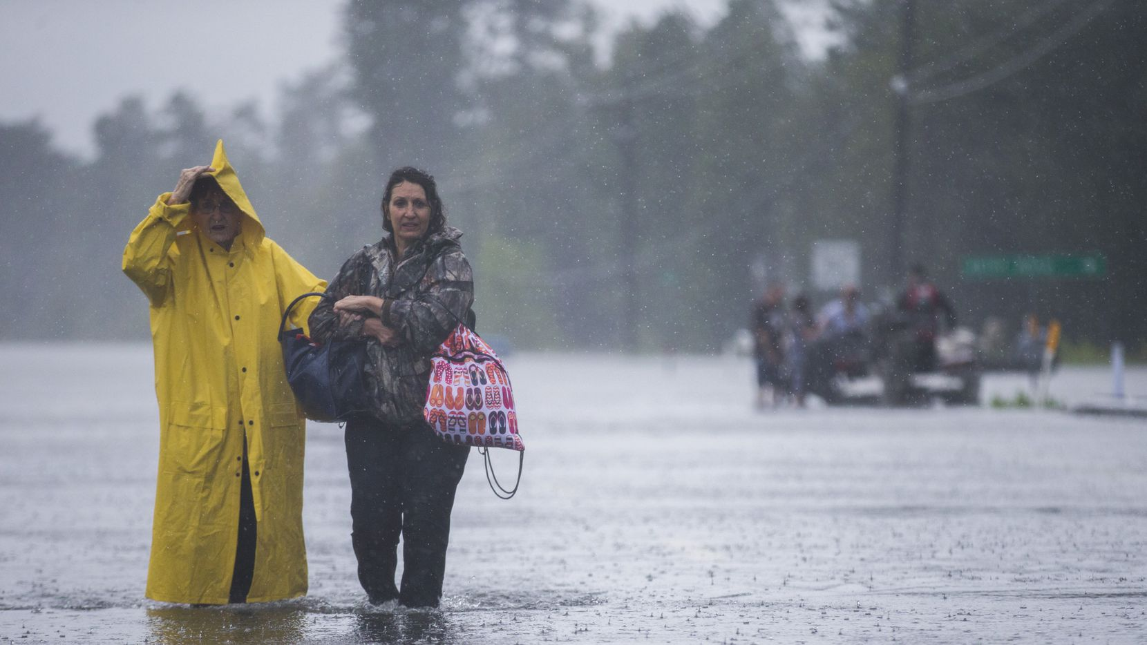 Rita Prosperie, left, and Connie McNeer walk out of flood waters to safety near Highway 96 on Wednesday, August 30 in Lumberton, Texas.
