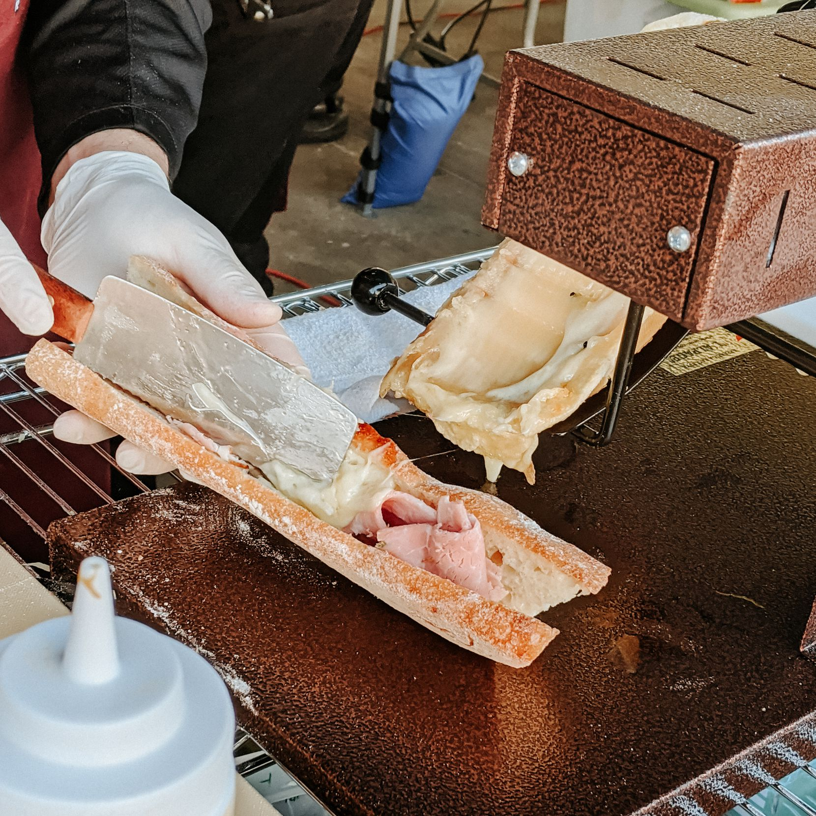 Rich Rogers of Scardello Artisan Cheese makes raclette sandwiches at the Dallas Farmers Market.
