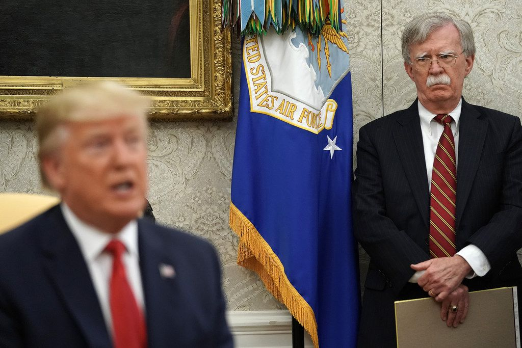Former national security adviser John Bolton (right) listens as President Donald Trump speaks at the White House earlier this summer. Trump said he will announce a new national security adviser next week.