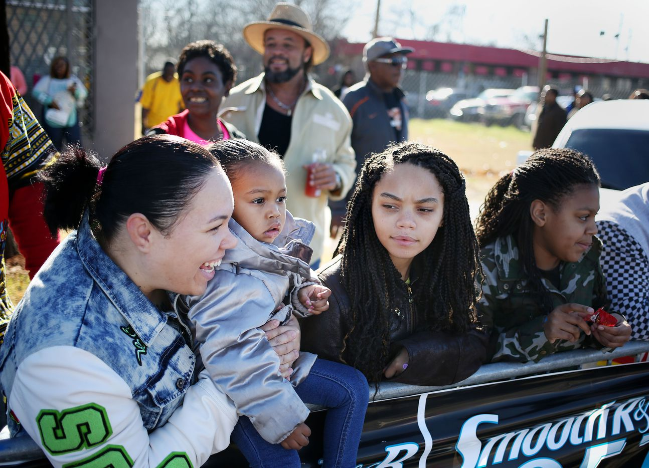 Jessica Flowers (left) holds her daughter Jyia Flowers, 2, while watching the parade.