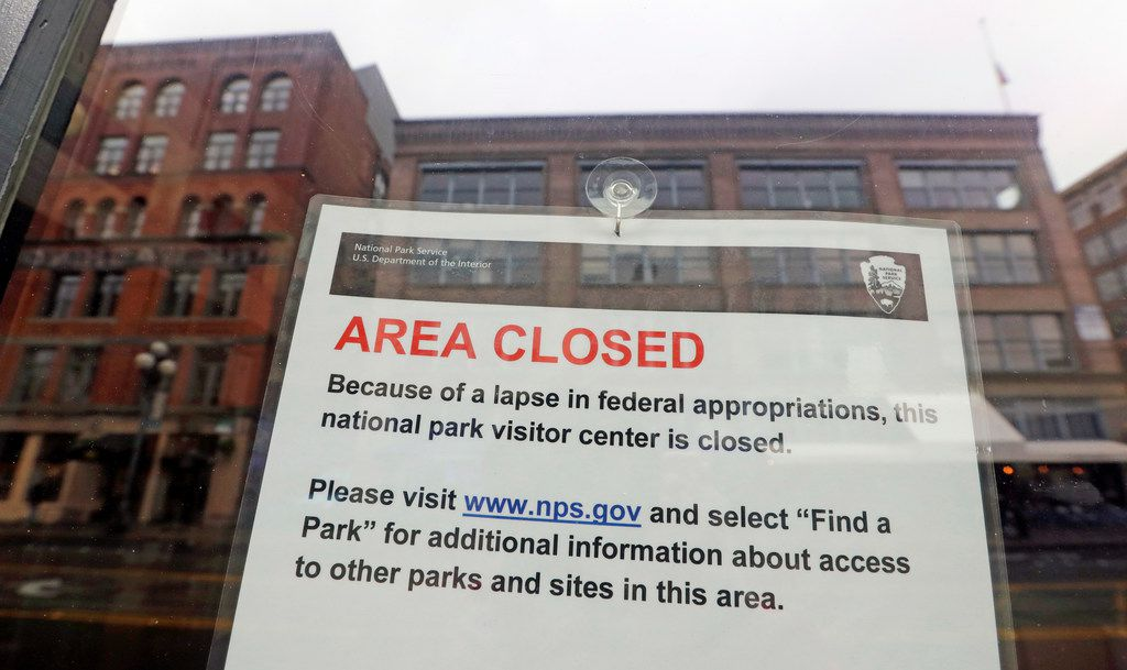 The tiny Klondike Gold Rush National Historical Park in Seattle's historic Pioneer Square neighborhood is posted with a closed sign as part of the federal government shutdown Wednesday, Dec. 26, 2018. The shutdown started Saturday when funding lapsed for nine Cabinet-level departments and dozens of agencies. (AP Photo/Elaine Thompson)