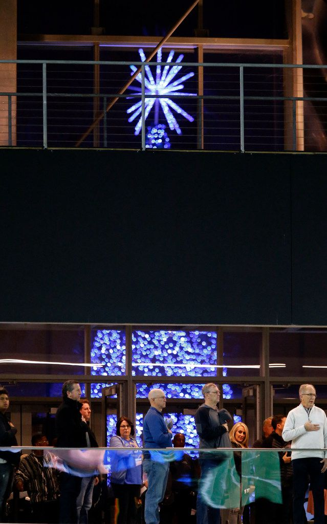 The Star Centre's giant Christmas tree can be seen through the Ford Center's window, as fans stand for the National Anthem in the foreground, before the start of the South Oak Cliff Vs. Frisco high school football playoff game at the Star on Friday, November 22, 2019. (John F. Rhodes / Special Contributor)