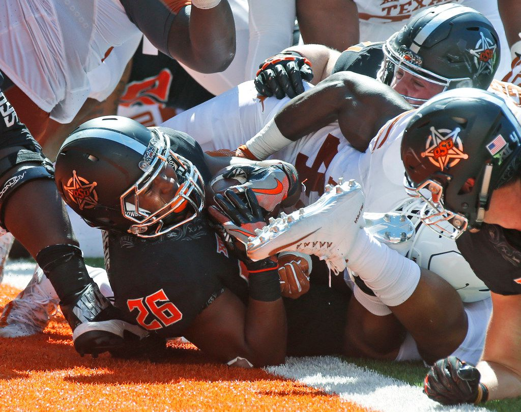 Oklahoma State running back Barry J. Sanders (26) pushes through for a touchdown against Texas in the third quarter of an NCAA college football game in Stillwater, Okla., Saturday, Oct. 1, 2016. Oklahoma State won 49-31. (AP Photo/Sue Ogrocki)