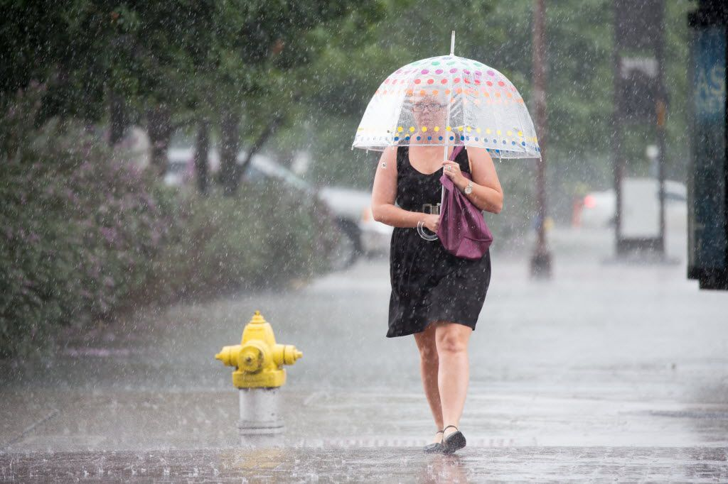 A pedestrian walks with an umbrella on the streets of downtown during Friday afternoon rainstorm on Aug. 26, 2016 in Dallas, Texas. (Ting Shen/The Dallas Morning News)
