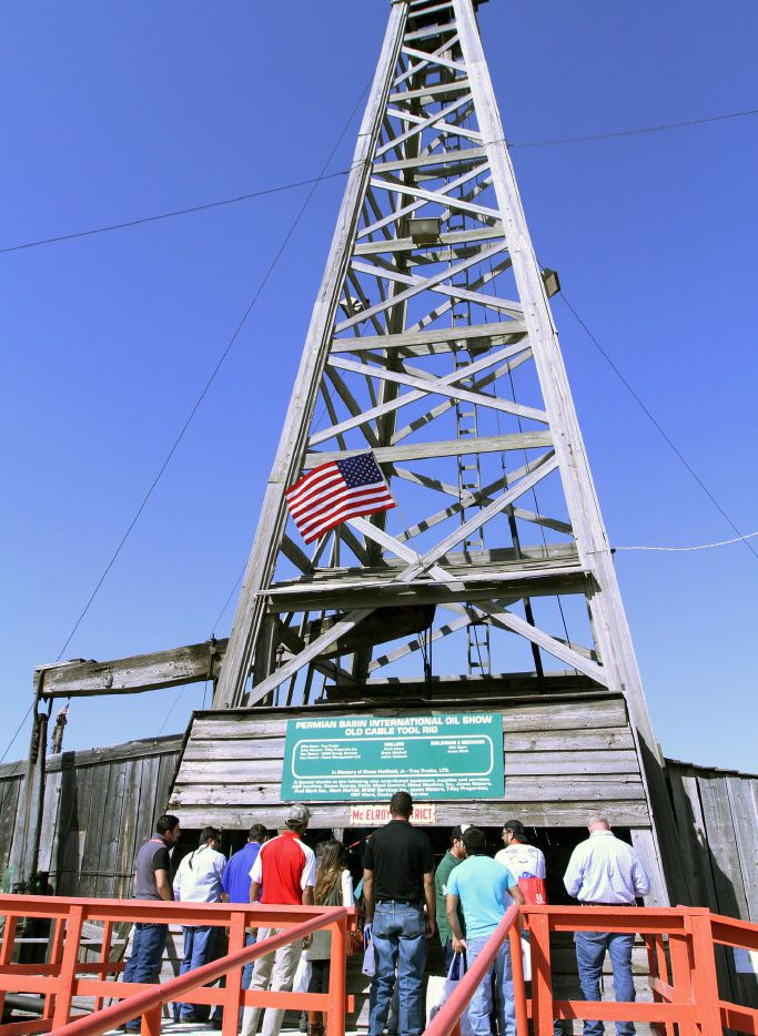 Permian Basin International Oil Show attendees examine the PBIOS Old Cable Tool Rig at Ector County Coliseum on Thursday, Oct. 20, 2016, in Odessa, Texas. (Jacob Ford/Odessa American via AP)