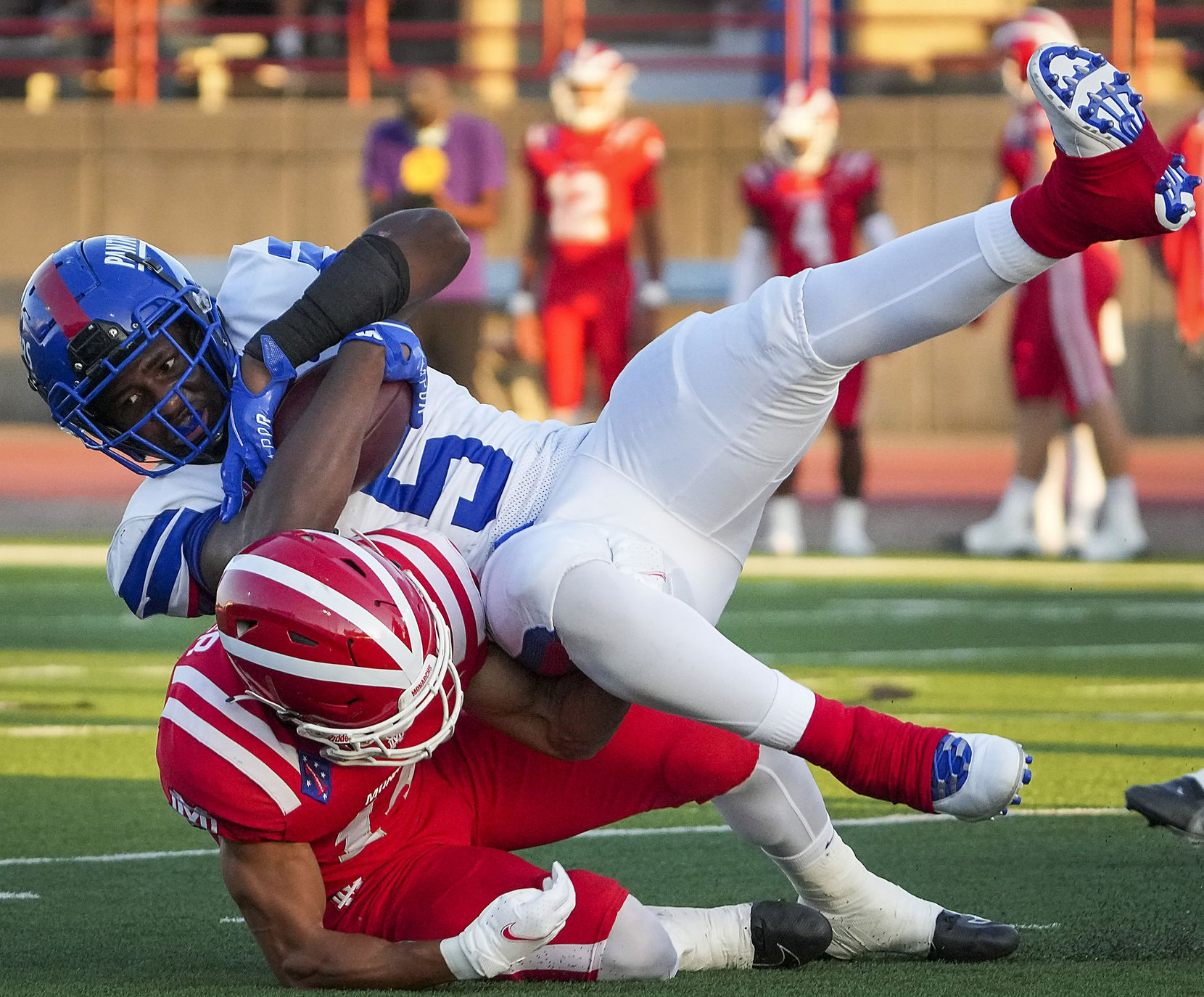 Duncanville running back Malachi Medlock (5) is knocked off his feet by Mater Dei defensive back Joshua Hunter (14) during the first half of a high school football game on Friday, Aug. 27, 2021, in Duncanville. (Smiley N. Pool/The Dallas Morning News)