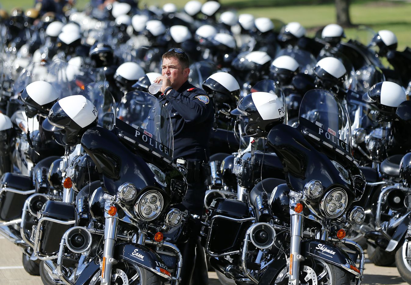 Colleyville motorcycle police officer Dustin Eason cools down with a drink of water as he waits for the funeral procession of fallen Dallas police officer Lorne Ahrens at Prestonwood Baptist Church in Plano, Wednesday, July 12, 2016.