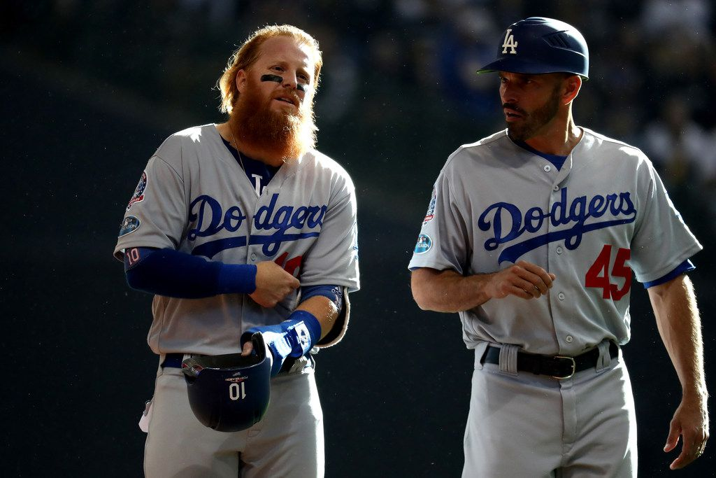 MILWAUKEE, WI - OCTOBER 13:  Justin Turner #10 of the Los Angeles Dodgers talks with third base coach Chris Woodward #45 against the Milwaukee Brewers in Game Two of the National League Championship Series at Miller Park on October 13, 2018 in Milwaukee, Wisconsin.  (Photo by Rob Carr/Getty Images)