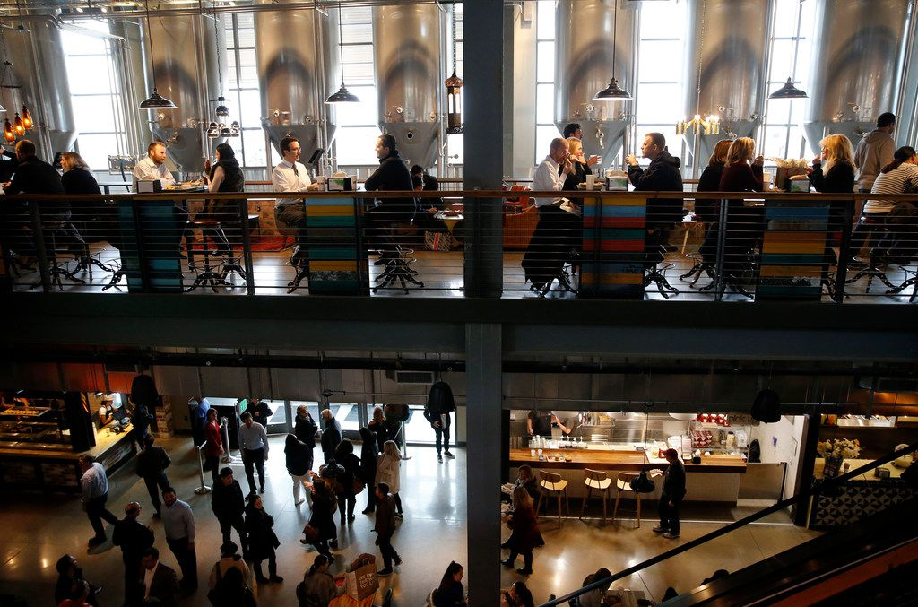 People eat lunch on multiple levels as others make their way inside Legacy Hall in Plano, on Thursday, December 7, 2017. Tanks from Unlawful Assembly Brewing Company can be seen in the background.