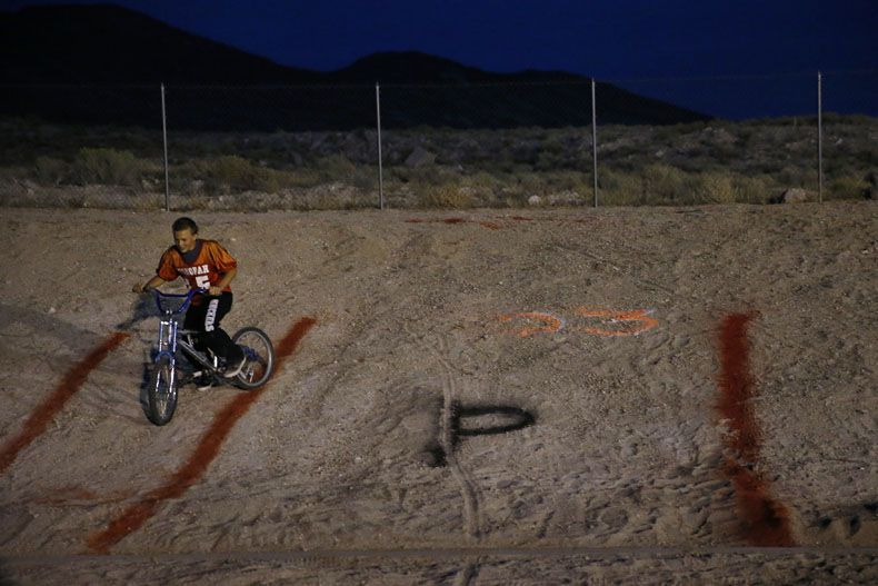 Kobe Bunker, 13, of Tonopah, Nevada, rides a bike on a hill in the football stadium during a high school football game between Sierra Lutheran and Tonopah in Tonopah, Nevada Friday August 28, 2015. Tonopah beat the team from Carson City, Nevada 55-26. (Andy Jacobsohn/The Dallas Morning News)