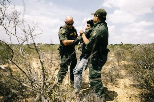 Los agentes de la Patrulla Fronteriza, Michael Johnson (izq) y Christian Salmon, detienen a un hombre de Honduras que cruzó el Río Grande en una bolsa inflable cerca de Roma, Texas. Foto WILLAIM WIDMER, THE NEW YORK TIMES