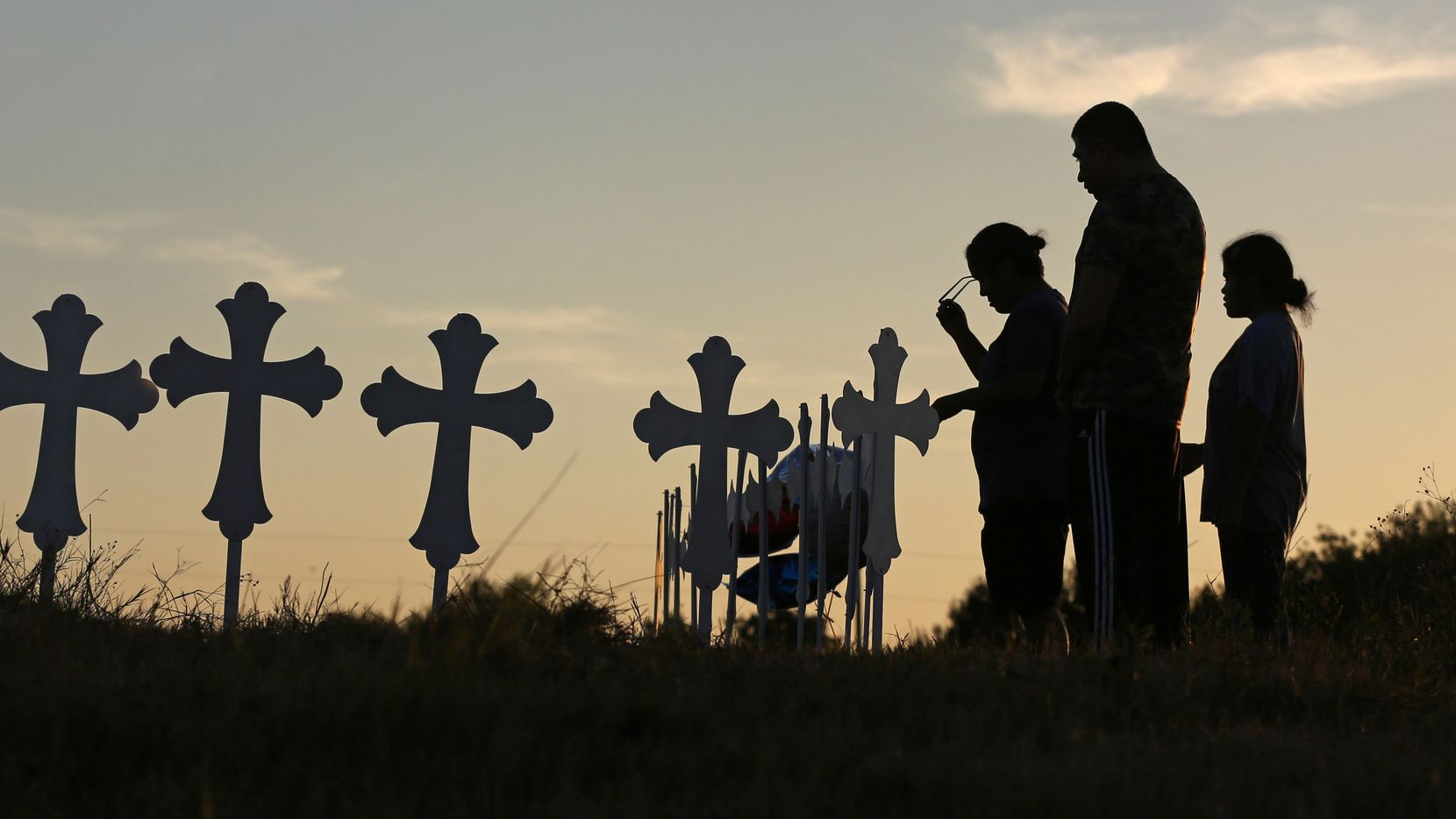 Irene and Kenneth Hernandez and their daughter Miranda Hernandez say a prayer in front of some of the 26 crosses placed in a field in Sutherland Springs, Texas to honor those who were killed in Sunday's mass shooting, when a gunman opened fire at a Baptist church in the small town southeast of San Antonio. Photographed on Monday, November 6, 2017.
