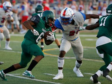 Kennedale's Cameron Hynson (6) rushes as Midlothian Heritage's D'Angelo Freeman (21) defends during the first half of their high school football game in Kennedale, Texas on September 6, 2019.