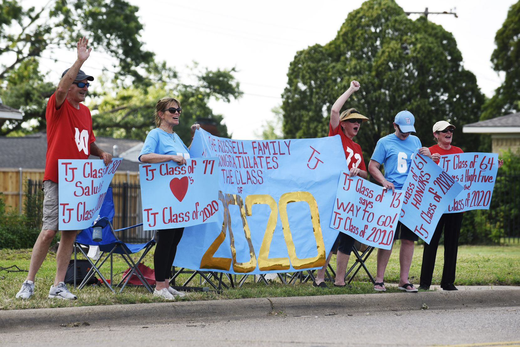 The Russell family and Thomas Jefferson High School alumni cheered for graduating TJ seniors during a parade outside the Dallas school on May 19. At the event, titled Senior Sunset, the seniors were handed personalized yard signs, prom goody bags and caps and gowns through rolled-down windows,