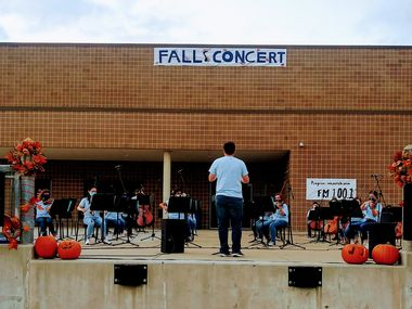 McKinney High School orchestra members perform on the school's loading dock during a concert that allowed the audience to remain in their cars and listen via FM radios.