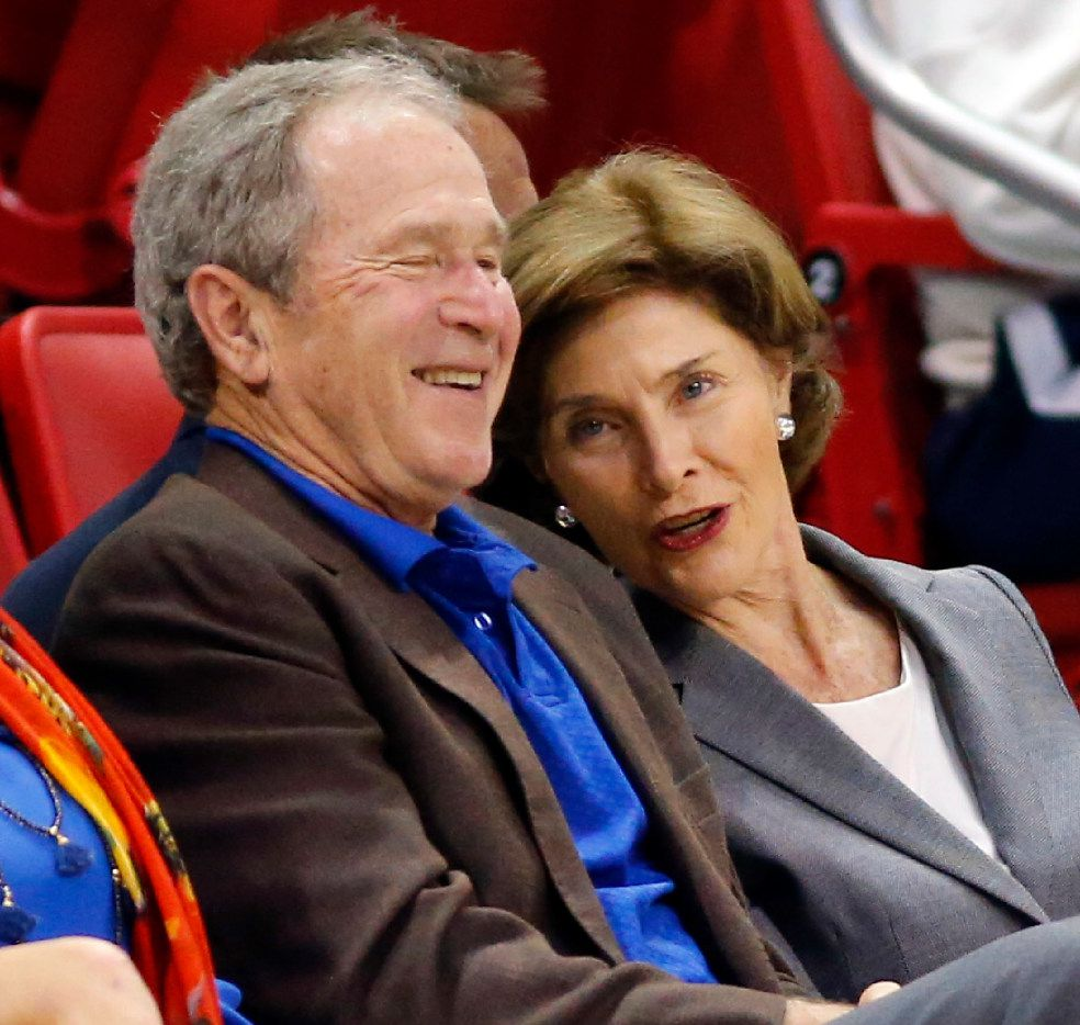 Former President George W. Bush shares a laugh with former First Lady Laura Bush during the first half of the Southern Methodist Mustangs.  (Tom Fox/The Dallas Morning News)