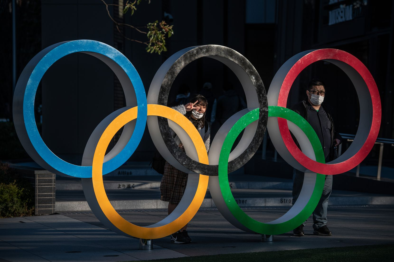 People wearing face masks pose for photographs next to Olympic Rings on March 24, 2020 in Tokyo, Japan.