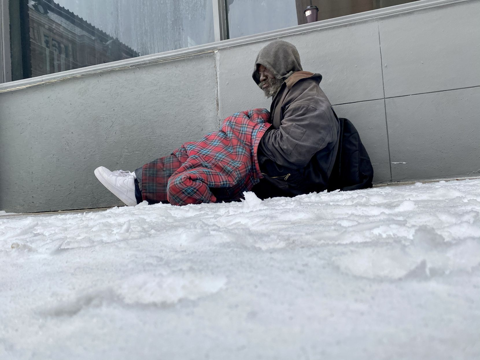 Darryl Davis sits on a grate to keep warm on Main Street early Wednesday morning February 17, 2021, in Dallas, Texas. He said he didn't want to go to the warming center at Kay Bailey Hutchison Convention Center.