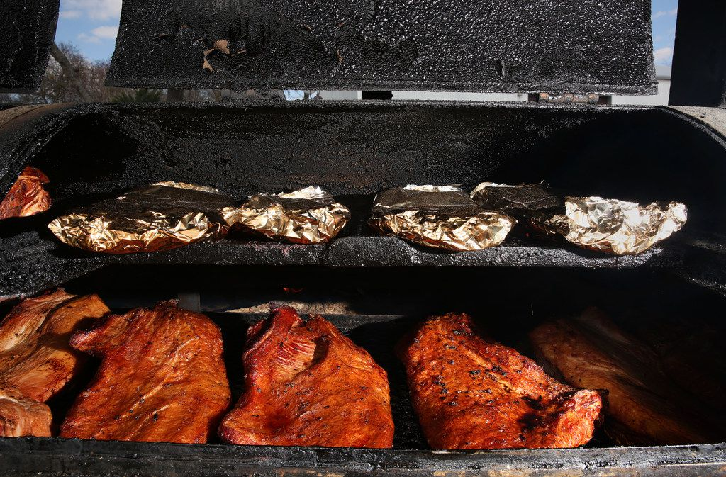 Beef and ribs wrapped in foil are cooked behind Franks Holy Smoke BBQ in Ovilla.
