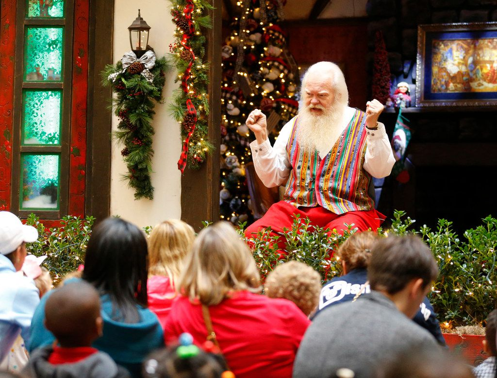 Santa Claus tells a story to children gathered outside his cottage house at NorthPark Center in Dallas on Dec. 13, 2018. For the past 30 years, Carl Anderson has portrayed Santa at NorthPark.