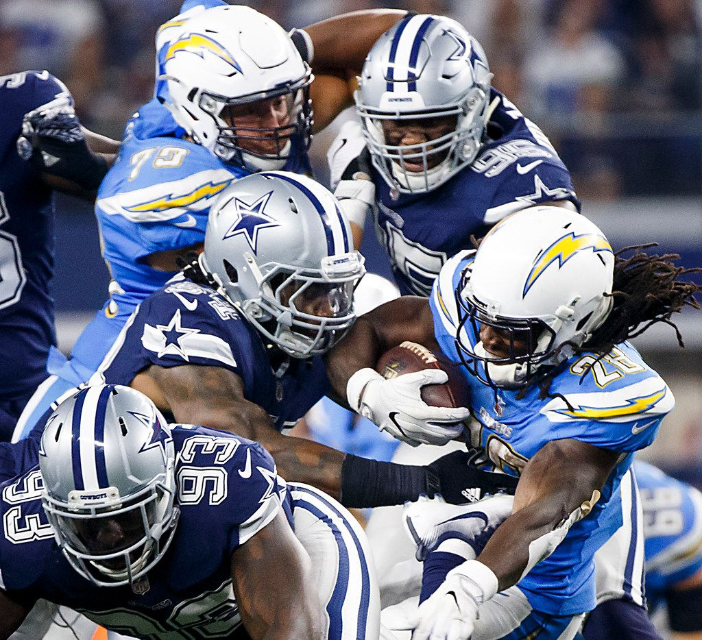 Los Angeles Chargers running back Melvin Gordon (28) is brought down by Dallas Cowboys outside linebacker Jaylon Smith (54) during the fourth quarter of an NFL football game at AT&T Stadium on Thursday, Nov. 23, 2017, in Arlington, Texas. The Chargers won the game 28-6.