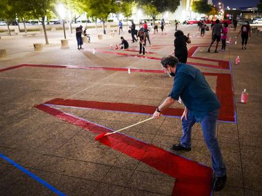 "Dallas Council Member Lee Kleinman joins volunteers in painting the words ""Black Lives Matter"" across the plaza in front of Dallas City Hall on June 8, 2020."