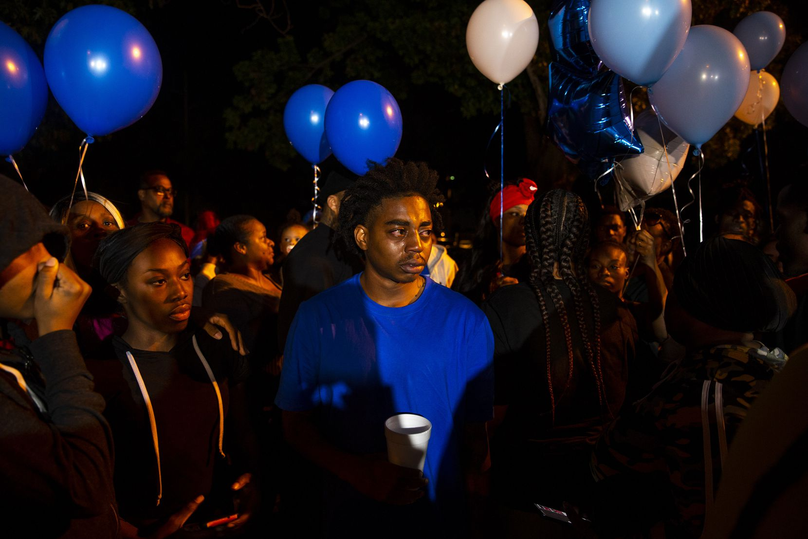 Family members take a moment before releasing balloons during a vigil for Kevin Berry Jr. on Sunday, October 27, 2019 at St. Augustine Park in Dallas. Kevin Berry Jr., whose nickname was Lil Wess, was one of the victims killed early Sunday morning when a gunman opened fire at a paerty near Greenville, Texas.