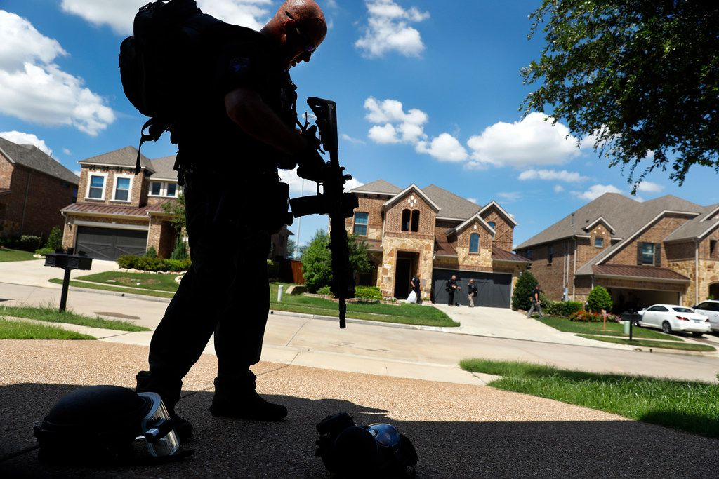 Irving SWAT team member Ryan Turner packs up his gear following a standoff with a barricaded man on San Marcos Drive in Irving.