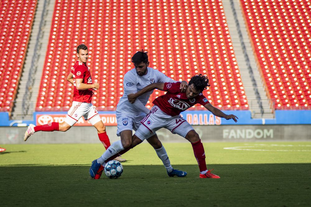 15 year old Jonathan Gomez of the FC Dallas Academy U17s, playing for professional developmental side North Texas SC, holds off an opposition player in a USL-1 game.