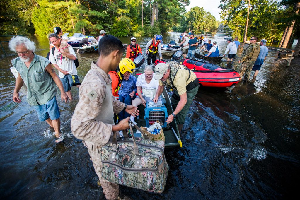Marines and members of a swift water rescue task force from Tampa, Florida prepare rescue boats on top of an amphibious assault vehicle to victims of flooding as a result of Tropical Storm Harvey in the Cooks Road area, one of the hardest hit areas in the county, on Thursday, August 31, 2017 near Lumberton, Texas. (Ashley Landis/The Dallas Morning News)