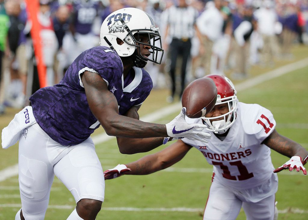 FILE - In this Oct. 20, 2018, file photo, TCU wide receiver Jalen Reagor (1) catches a pass in the end zone for a touchdown as Oklahoma cornerback Parnell Motley (11) defends during the first half of an NCAA college football game in Fort Worth, Texas. TCU has one of the Big 12's best playmakers in speedy receiver Reagor. The Horned Frogs have to determine who will get him the ball, with several options in the quarterback mix. (AP Photo/Brandon Wade, file)