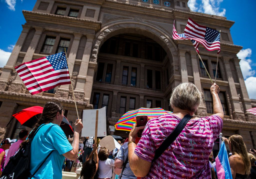 Protestors wave American flags during a One Texas Resistance rally on the south steps of the capitol on the first day of a legislative special session on Tuesday, July 18, 2017 at the Texas state capitol in Austin, Texas. (Ashley Landis/The Dallas Morning News)