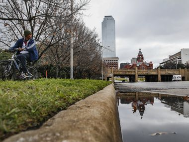 A bicyclist passes by Martyrs Park on Thursday, Jan. 23, 2020 in Dallas.