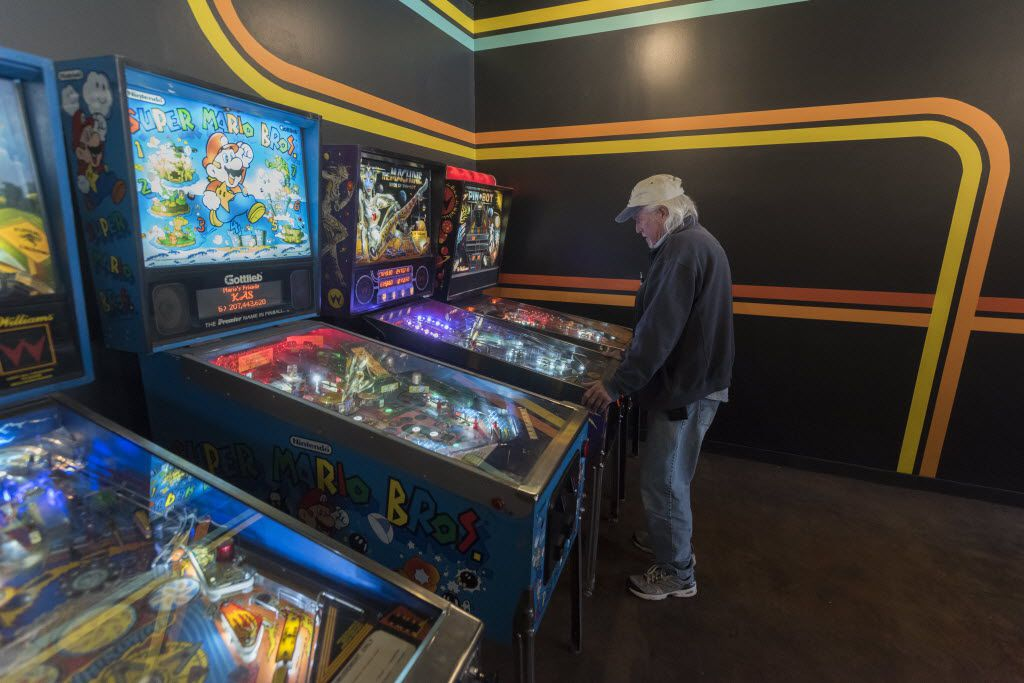 Will Hyden plays pin ball at  Free Play, a retro arcade in Richardson on Friday, Dec. 4, 2015. His son, Corey Hyden, is one of the owners.
