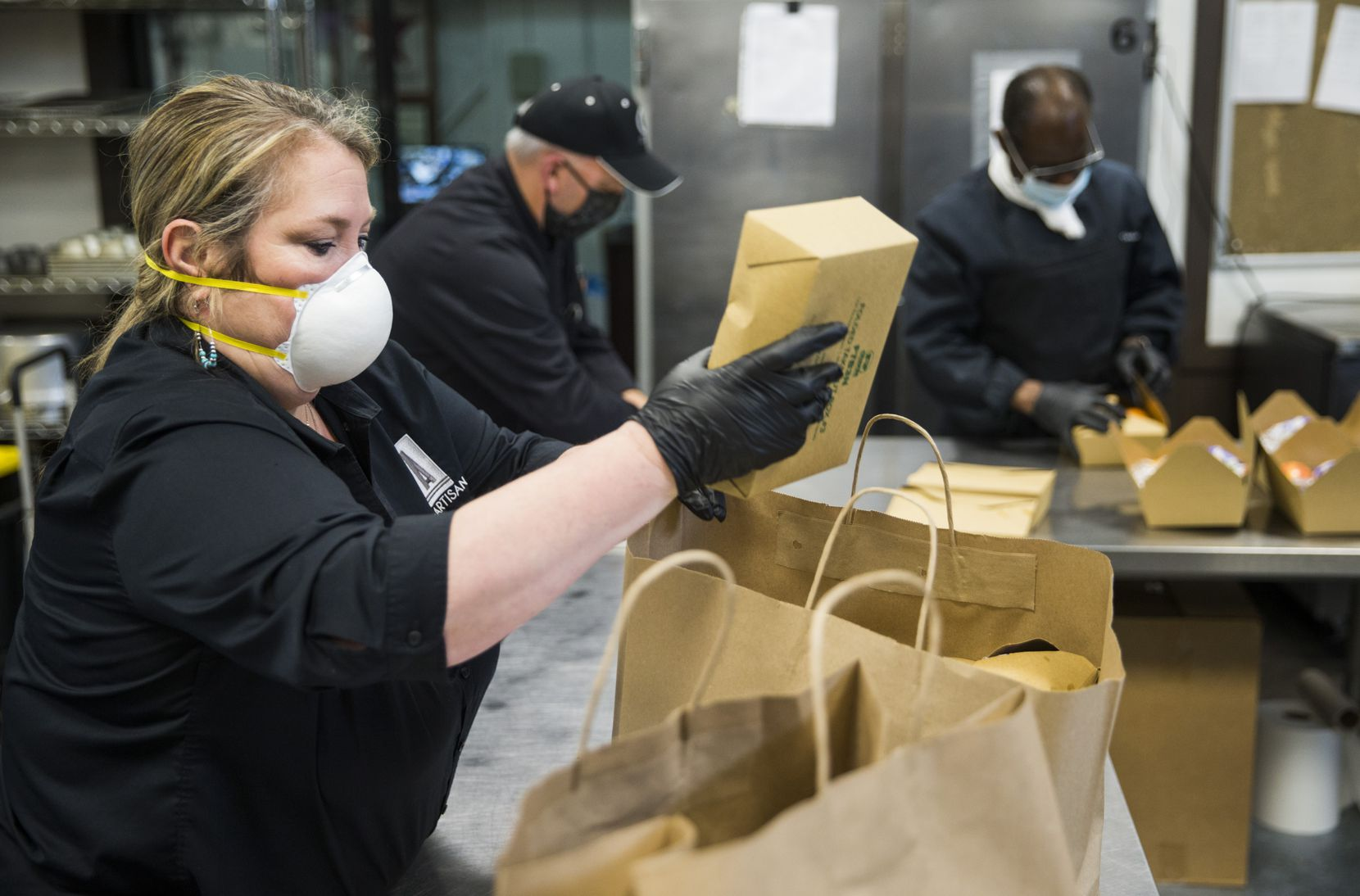 From left, Trisha Snell, John Gilbert, and Bill Jordan of G-Texas Custom Catering pack box lunches for Austin Street Shelter on Saturday, April 11, 2020 at G-Texas Custom Catering in Dallas.