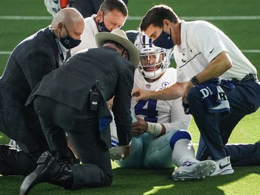 Dallas Cowboys quarterback Dak Prescott receives medical attention after being injured on a tackle by New York Giants cornerback Logan Ryan during the third quarter of an NFL football game at AT&T Stadium on Sunday, Oct. 11, 2020, in Arlington.
