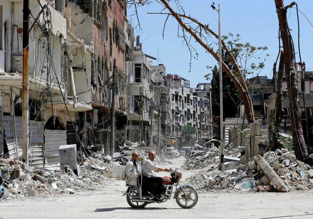 Syrians ride a motorbike along a destroyed street in Douma on the outskirts of Damascus on April 16, 2018 during an organised media tour after the Syrian army declared that all anti-regime forces have left Eastern Ghouta, following a blistering two month offensive on the rebel enclave.   The announcement, which represents a key strategic victory for President Bashar al-Assad, came just hours after US-led strikes pounded Syrian government targets in response to a suspected chemical attack on the enclave's main town of Douma.