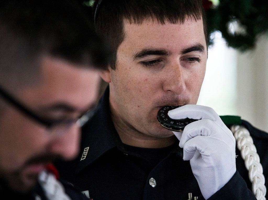 Senior corporal Ryan Cordova, of the Dallas Police Choir, uses a pitch pipe before performing at Richardson Woman's Club on Dec. 6, 2018. The choir is kicking off its 2018 Christmas Tour performing at hospitals, assisted living centers and other businesses.