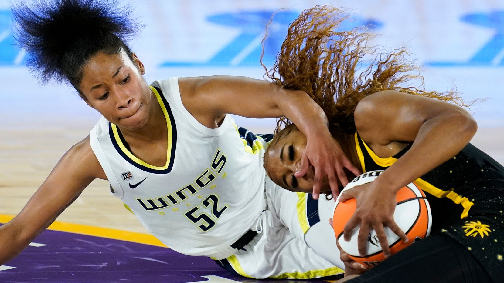 Dallas Wings guard Tyasha Harris (52) covers the face of Los Angeles Sparks guard Te'a Cooper (2) while reaching for the ball on the floor during the second quarter of a WBNA basketball game Friday, May 14, 2021, in Los Angeles.