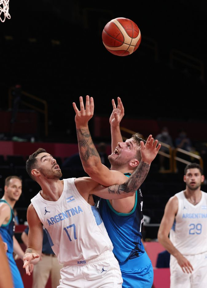 Slovenia's Luka Doncic (77) and Argentina's Luca Vildoza (17) go after the ball for a rebound in the first half of play during the postponed 2020 Tokyo Olympics at Saitama Super Arena on Monday, July 26, 2021, in Saitama, Japan. Slovenia defeated Argentina 118-100. (Vernon Bryant/The Dallas Morning News)